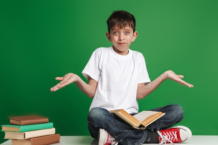 Cute little boy with freckles studying, sitting with stack of books over green