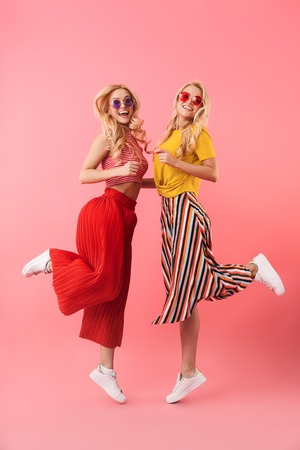 Full length image of Cheerful blonde twins in sunglasses having fun together and looking at the camera over pink background