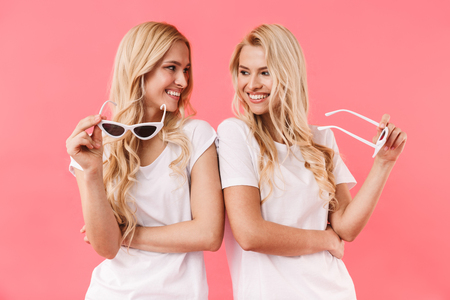 Happy blonde twins wearing in t-shirts posing with sunnglasses and looking to each other over pink background