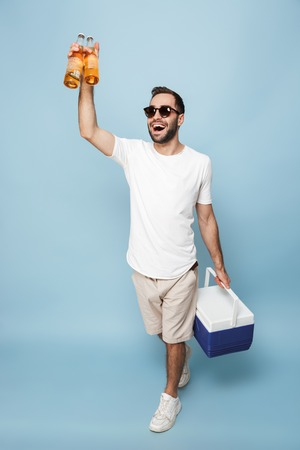 Full length of a cheerful excited man wearing blank t-shirt standing isolated over blue background, carrying cooler with cold beer Stock Photo