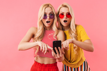 Shocked blonde twins in sunglasses using smartphone and looking at the camera over pink background