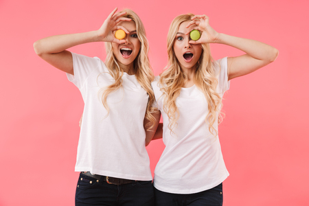 Funny blonde twins wearing in t-shirts having fun with cakes and looking at the camera over pink background Banco de Imagens