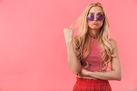 Portrait of a confused blonde woman wearing summer clothes standing isolated over pink Archivio Fotografico - 124174737
