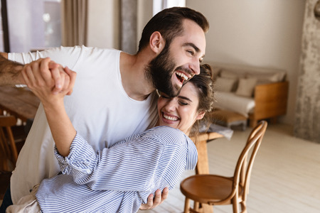 Photo of laughing brunette couple in love man and woman 20s smiling while hugging together in apartment