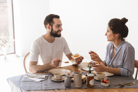 Image of brunette couple in love man and woman 20s eating breakfast together while sitting at table in apartment Archivio Fotografico - 124699652