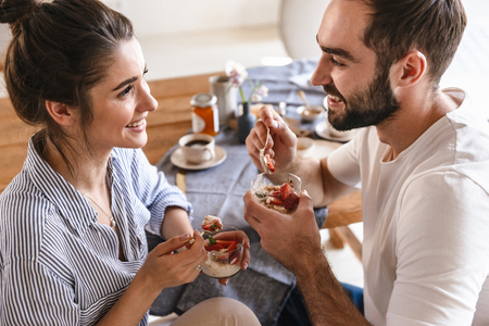 Image of caucasian brunette couple man and woman 20s eating panna cotta dessert together while sitting at table at home Archivio Fotografico - 124699387