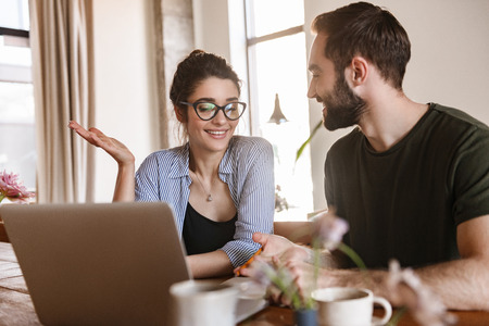 Image of businesslike brunette couple man and woman 20s drinking coffee and working on laptop together while sitting at table at home Archivio Fotografico - 124699385