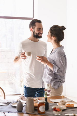 Image of cheery brunette couple man and woman 20s drinking coffee together while having breakfast in apartment Archivio Fotografico - 124699386