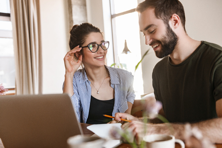 Image of joyful brunette couple man and woman 20s drinking coffee and working on laptop together while sitting at table at home Archivio Fotografico - 124699388