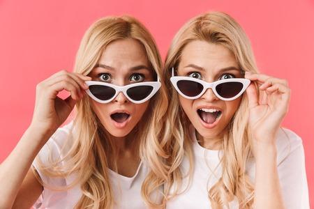 Geschokte blonde tweeling doet een zonnebril af en kijkt naar de camera over roze