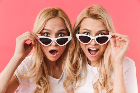 Shocked blonde twins take off sunglasses and looking at the camera over pink