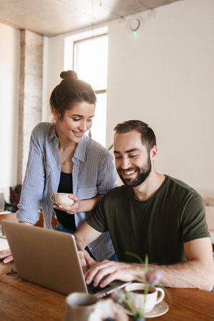 Image of pleased brunette couple man and woman 20s drinking coffee and working on laptop together while sitting at table at home