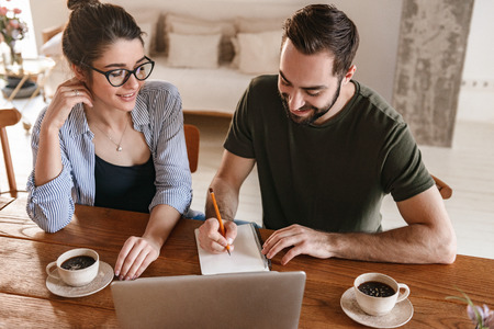 Image of happy brunette couple man and woman 20s drinking coffee and working on laptop together while sitting at table at home Archivio Fotografico - 124699400