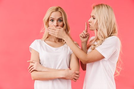Deux belles jeunes sœurs jumelles isolées sur fond rose, montrant un geste de silence Banque d'images
