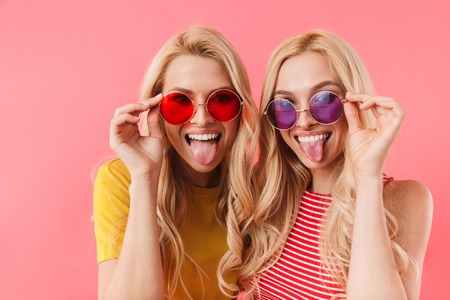 Funny blonde twins in sunglasses having fun while showing their tongues and looking at the camera over pink background