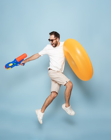 Full length of a cheerful excited man wearing blank t-shirt jumping isolated over blue background, having fun with inflatable ring and water gun