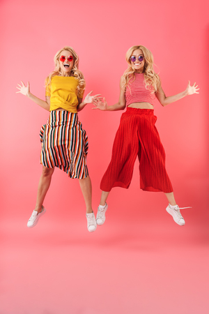 Full length image of Happy blonde twins in sunglasses jumping and looking at the camera over pink background 스톡 콘텐츠