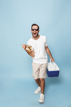 Full length of a cheerful excited man wearing blank t-shirt standing isolated over blue background, carrying cooler with cold beer Stockfoto
