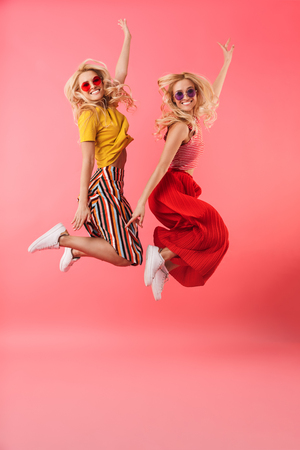 Full length image of Cheerful blonde twins in sunglasses jumping and looking at the camera over pink background
