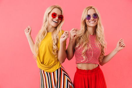 Picture of Pleased blonde twins in sunglasses having fun and dancing over pink background