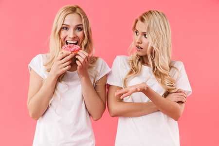 Happy blonde woman eating donut and looking at the camera while her displeased sister looking at her over pink background 版權商用圖片