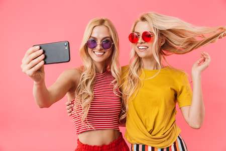 Smiling blonde twins in sunglasses having fun while making selfie on smartphone over pink background