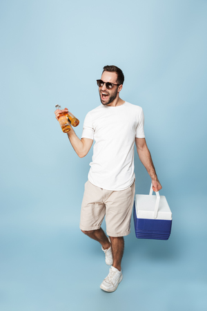 Full length of a cheerful excited man wearing blank t-shirt standing isolated over blue background, carrying cooler with cold beer