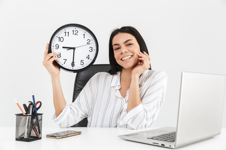 Attractive smiling young businesswoman sitting at the desk isolated over white background, showing wall clock Banque d'images - 124565885