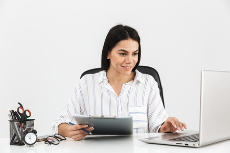 Attractive young businesswoman sitting at the desk isolated over white background, working with laptop computer and documents