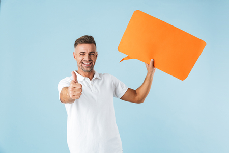 Photo of a handsome excited emotional adult man posing isolated over blue wall background holding speech bubble make thumbs up. Stockfoto