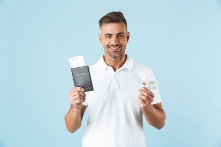 Image of a handsome excited emotional adult man posing isolated over blue wall background holding passport with tickets and credit card.