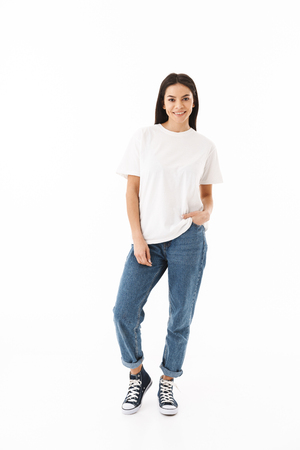 Full length of a smiling young casual woman standing isolated over white background Banco de Imagens