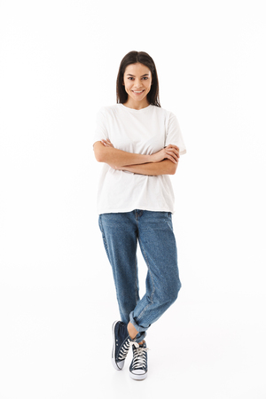 Full length of a smiling young casual woman standing isolated over white background, arms folded