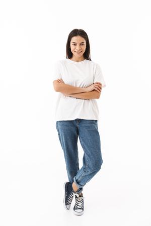 Longitud total de una mujer casual joven sonriente que se encuentran aisladas sobre fondo blanco, con los brazos cruzados