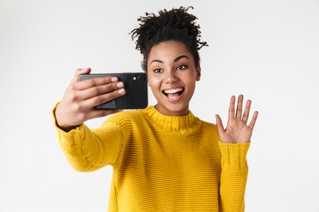 Image of a beautiful young african excited emotional woman posing isolated over white wall background talking by mobile phone take a selfie waving. Banco de Imagens