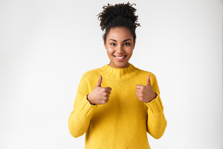 Photo of a beautiful young african happy woman posing isolated over white wall background make thumbs up.