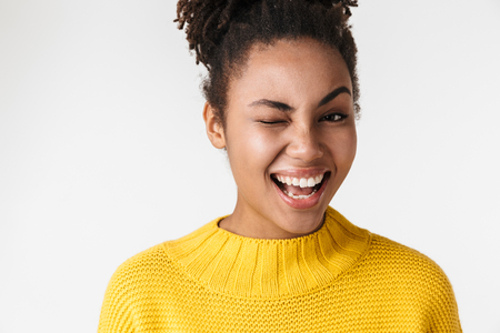 Image of a beautiful young african happy excited emotional woman posing isolated over white wall background winking.