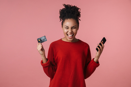Image of a beautiful amazing shocked excited young african woman posing isolated over pink wall background using mobile phone make winner gesture holding credit card.