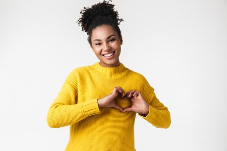 Photo of a beautiful young african emotional woman posing isolated over white wall background make heart love gesture.