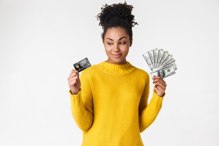 Image of a beautiful young african thinking woman posing isolated over white wall background holding money and credit card.