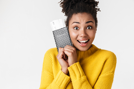 Image of a beautiful young african excited emotional happy woman posing isolated over white wall background holding passport with tickets.