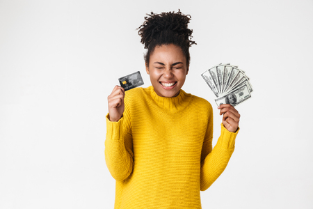 Image of a beautiful young african excited emotional happy woman posing isolated over white wall background holding money and credit card. Imagens