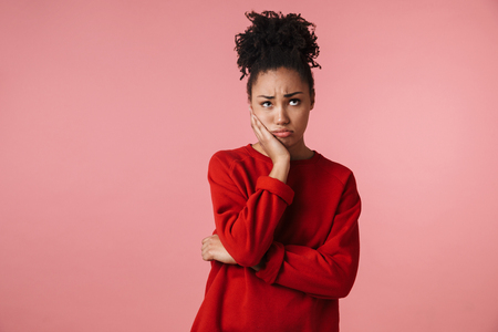 Image of a beautiful amazing sad confused young african woman posing isolated over pink wall background. Imagens