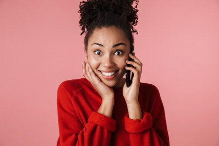 Image of a beautiful amazing happy excited young african woman posing isolated over pink wall background talking by mobile phone.