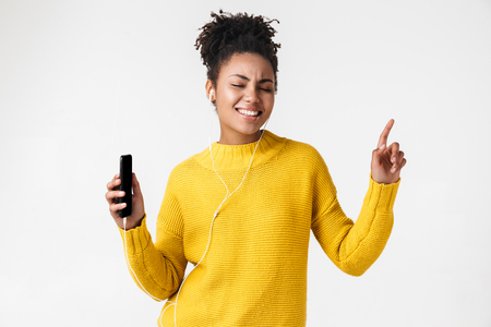 Image of a beautiful young african excited emotional happy woman posing isolated over white wall background listening music with earphones using mobile phone.