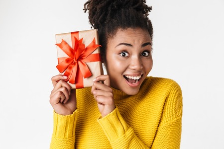 Image of a beautiful young african excited emotional happy woman posing isolated over white wall background holding present gift box.