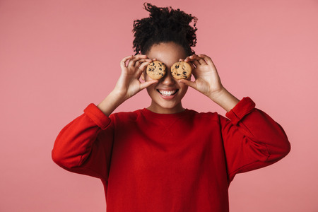 Image of a beautiful amazing happy excited young african woman posing isolated over pink wall background holding sweeties cookies.