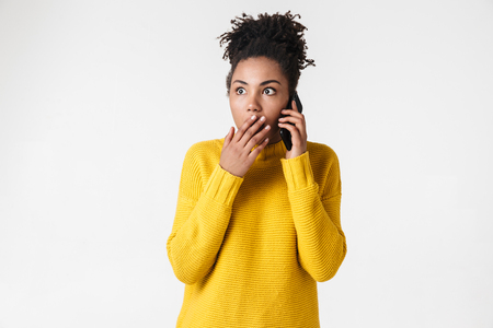 Image of a beautiful young african excited emotional shocked woman posing isolated over white wall background talking by mobile phone.