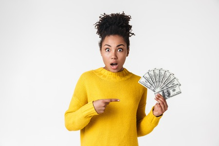 Image of a beautiful young african excited emotional happy woman posing isolated over white wall background holding money pointing. Imagens