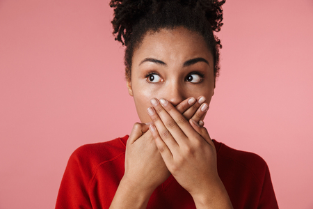 Image of a beautiful amazing shocked scared young african woman posing isolated over pink wall background covering mouth.